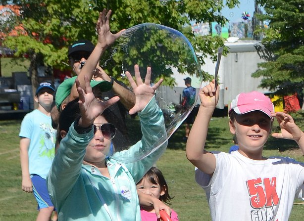 very large bubbles being made in front of a crowd of children and adults, kids chasing and trying to catch and burst the bubbles, just at the moment that the bubble breaks