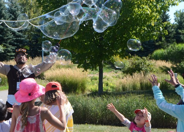 very large bubbles being made in front of a crowd of children and adults, kids chasing and trying to catch and burst the bubbles, small girl with her arms outstretched