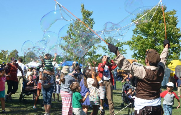 very large bubbles being made in front of a crowd of children and adults, kids chasing and trying to catch and burst the bubbles