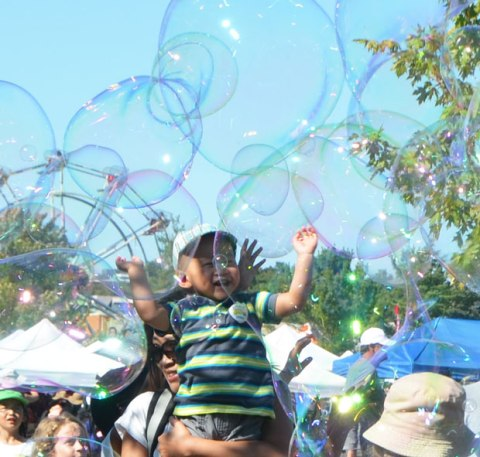 very large bubbles being made in front of a crowd of children and adults, kids chasing and trying to catch and burst the bubbles, young boy being held up by his mother to reach the bubbles
