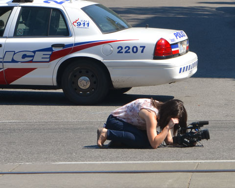 a camera woman has her camera on the ground and she is kneeling behind it and trying to take a picture. She is bare footed. There is a police car parked behind her. She is on the street, photographing a parade