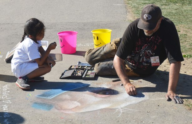 man is drawing a picture with chalk on the sidewalk. A little girl is squatting beside him and watching him work