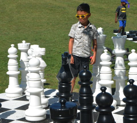 a young boy with bright yellow rimmed sunglasses stands on a large chess board contemplating his next move in the game of chess.