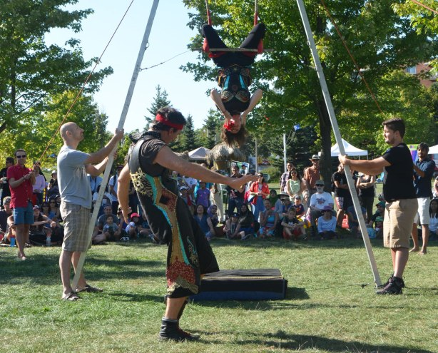 busker show, men holding up a trapeze frame while and couple perform on it.