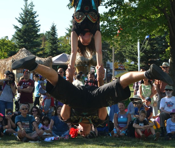 acrobatics - a woman upside known hanging from a trapeze by her knees, holds onto a man