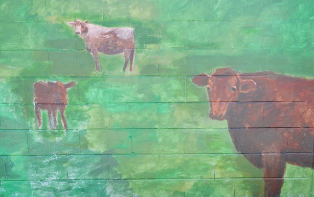 painting of three brown cows in a green field, painted on a garage door