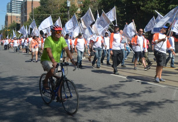 a male cyclist rides past men marching in a labour day parade all carrying white Liuna union flags