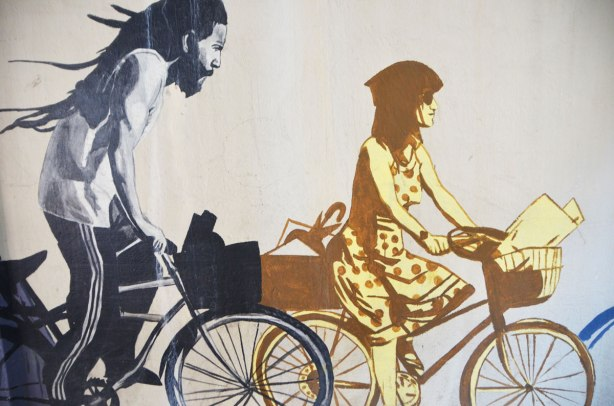 part of a mural called Strength in Numbers, on a wall, a painting of two cyclists. One is a black man with dreadlocks and the other is a woman in a polka dot dress with a box on the back of her bike.