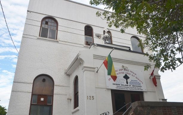 front of a white building, two storeys, with round top windows, two flags flying by the door. Sign says Debre Selam St. Michael Ethiopian Orthodox Tewahedo Church. Small cross above the entranceway