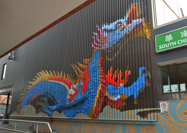 mural of a large blue dragon on a wall, outrside, with red and gold coloured spines