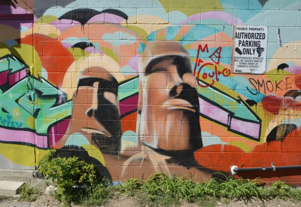 part of a mural on a wall showing two Easter Island type heads