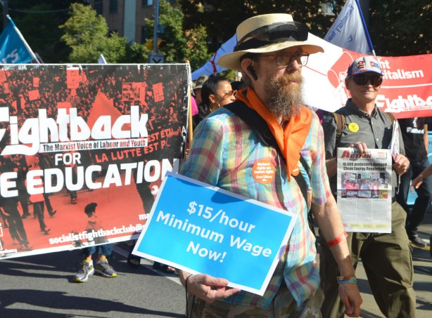a man with a large beard, wearing a straw hat and an orange bandana around his neck, carries a sign that says $15/hour minimum wage now, in a parade. behind him is a banner protesting the cost of university education and demanding free university education