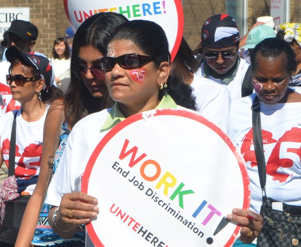 a group of women walking in a labour day parade.  One has a red heart with the number 75 inthe middle of it painted on her cheek.  She is also holding a circular sign that says Work It! End job discrimination.  Unite here.