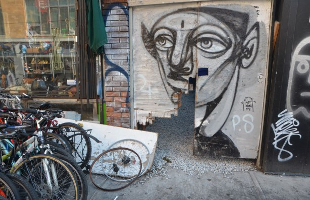 anser face on an old wood gate that is wearing out, broken across the bottom. bikes parked to the left of the gate