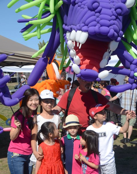 a large monster made of purple, red and green balloons is manned by a man, an Asian family is having their picture taken in front of the monster
