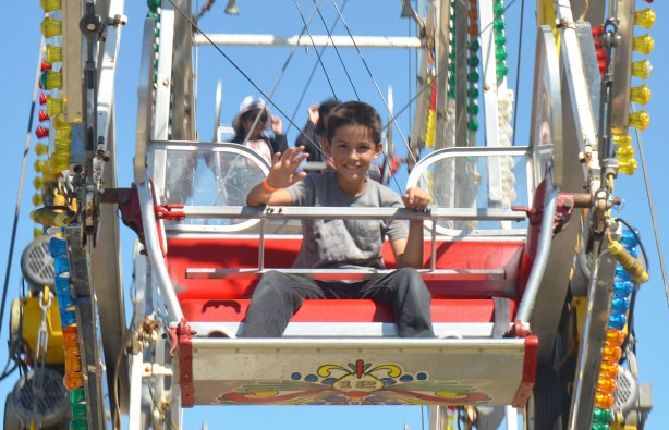 a boy is waving to the camera as he sits on a ferris wheel