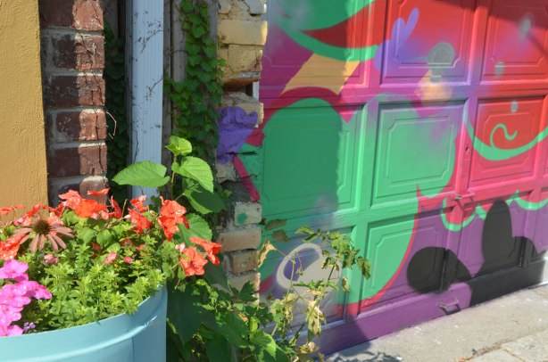 an old blue plastic barrel that has been turned into a planter, with pink flowers and greenery, in front of a garage door that has been painted in abstract street art in bright colours.