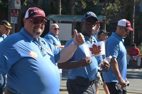 men in light blue T-shirts and wearing baseball caps, pass by in a parade, one is holding a small union flag (amalgamated transit union) and one is giving a thumbs up