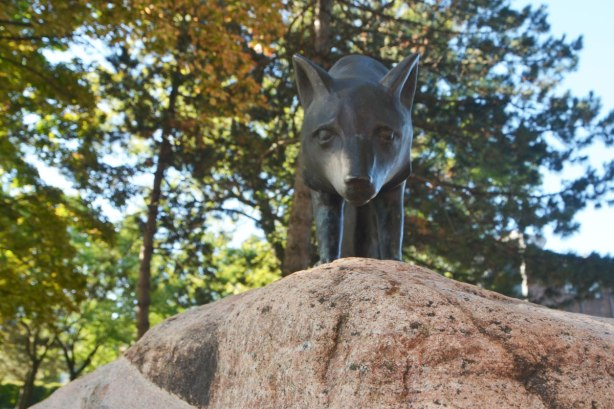a small sculpture of a fox on top of a rock. The fox seems to be looking right into the camera
