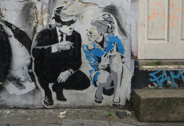 paste up of two people crouching beside a door.