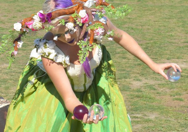 a woman is dressed as Gaia with flowers in her hair, balancing and juggling three glass balls