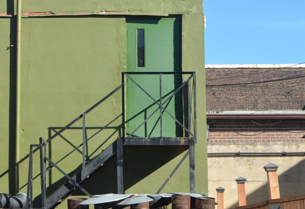 green second story door at top of metal exterior staircase, on a wall that is a different shade of green