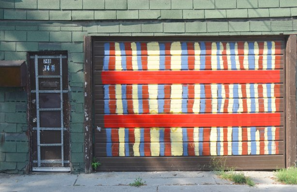 a garage door painted in yellow, red and blue vertical stripes as well as two wide horizontal stripes, the walls are green shingle and the entry door is black with a grid of metal stripping on it.