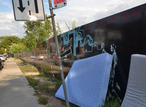 two old mattresses lean against a fence that has been painted with a mural in black, red and light blue.   Along a sidewalk with cars parked beside, a few small trees.