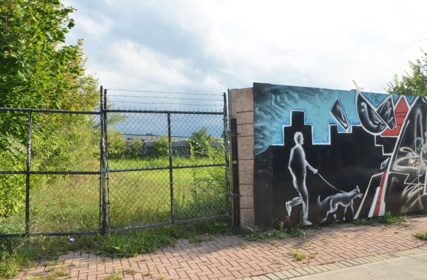 chain link fence with barbed wire above it on the left side and then a wood fence on the right, wood fence has been painted with a mural and here in the mural is a man walking a dog past a building