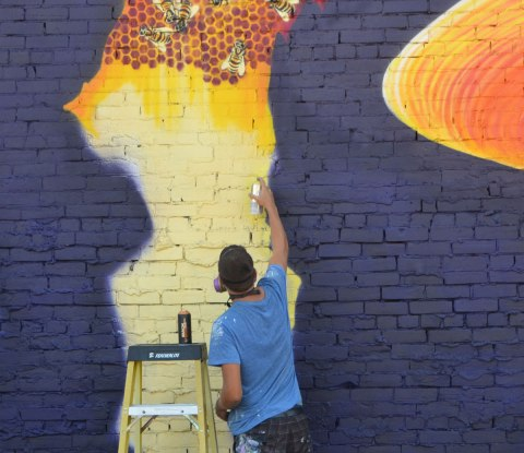 a man is painting a mural, this part is a honeycomb with some bees on it. Dark blue background.
