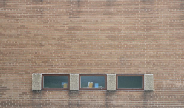 three windows arrange horizontally in a brick wall. windows are not high