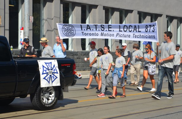 a group of people in grey t-shirts walk behind a black pick up truck in a parade, carrying a banner that says IATSE LOcal 873 union, Toronto Motion Picture Technicians.