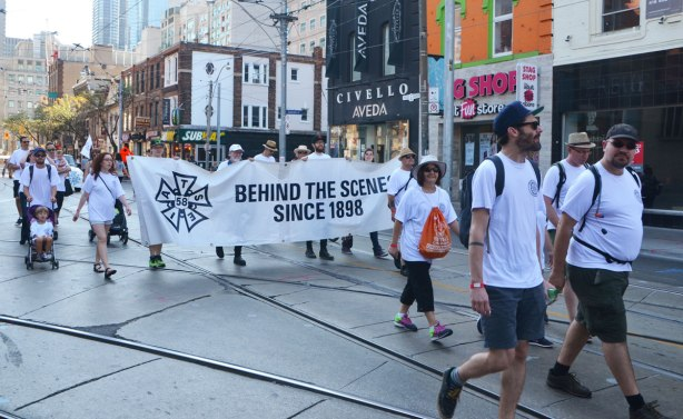 iatse 58, union members walk in a labour day parade with their banner that says Behind the Scenes since 1898