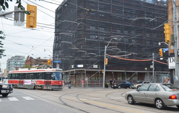 intersection, TTC street car turning left, a grey car near the intersection, a few pedestrians, a large building wrapped in black netting as the building is being cleaned and renovated.