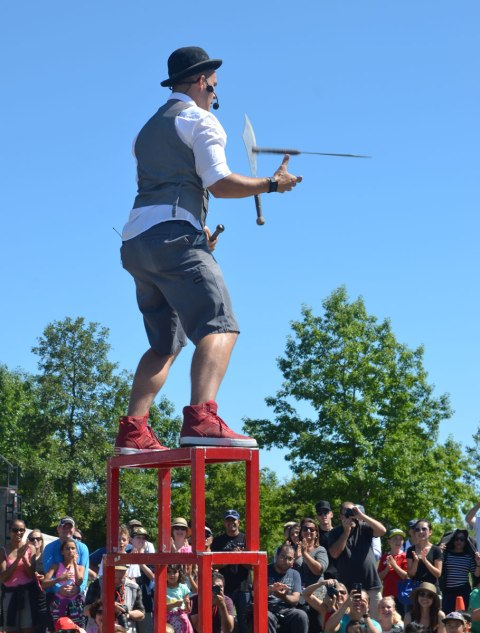 a man stands on top of three stools as he juggles three knives