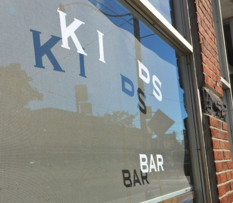 window of a coffee shop where some of the letters have been removed. It now says Kids Bar. Shadows of the letters are on the blind that covers the inside of the window of the now closed shop