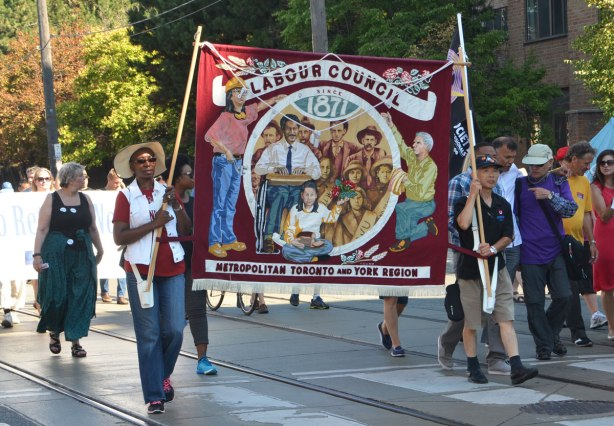 two people are carrying a banner for the Labour Council of Metropolitan Toronto and York Region in a parade. others are walking beside and behind them