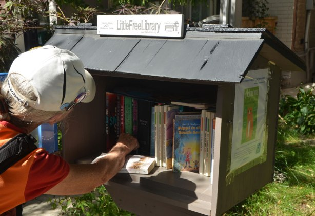 a woman in a white baseball cap is reaching into a 'little free library' shelf of books outside a house