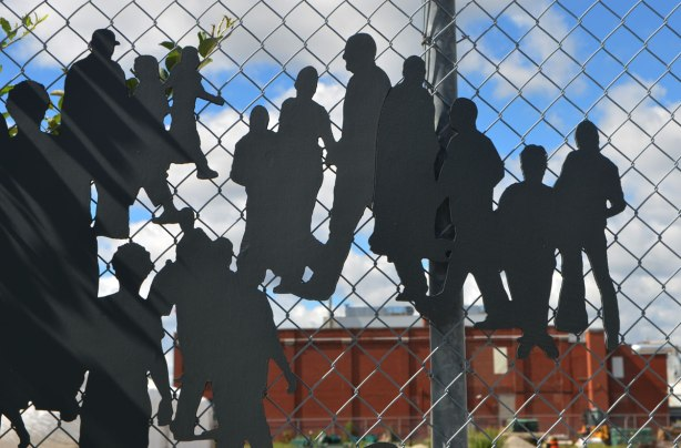 metal cutout figures of people walking, alongside a chainlink fence as part of an art installation