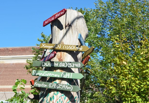 an old tree trunk has been turned into a support for many little arrow shaped signs that point the direction to cities around the world along with how many kilometres it is to those cities.