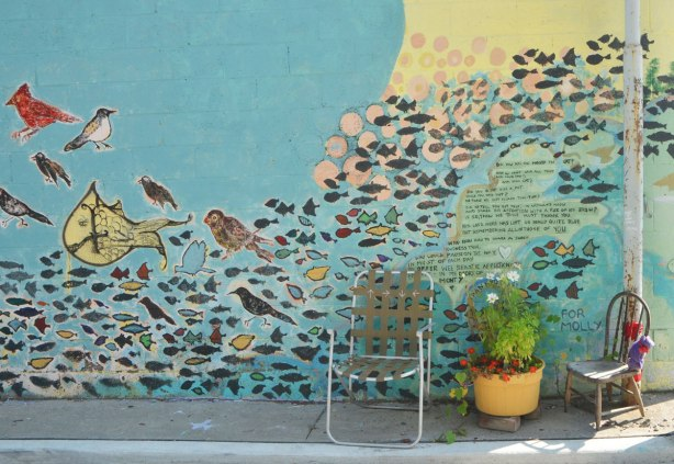 mural on a wall with lots of birds and fish and a poem as a memorial to a cat, with two chairs in front of it as well as a yellow planter with flowers in it.