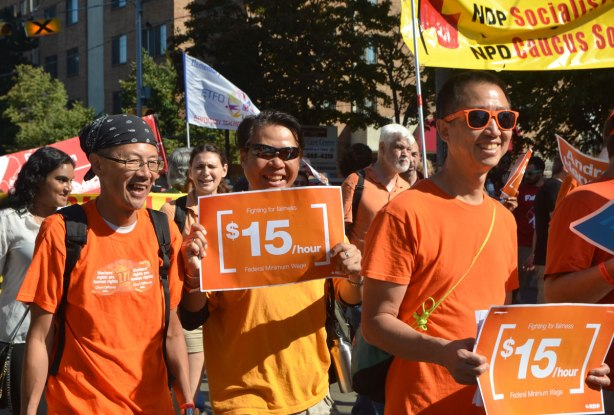 a group of people walking in a Labout Day parade, wearing orange T-shirts and holding orange signs protesting for fifteen dollars per hour minimum wage