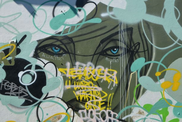 street art painting of part of a woman's face by anser, on olive green backgound, partially painted over and with words written in front of it.