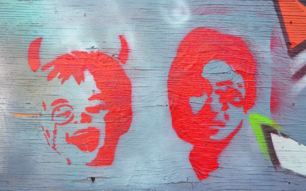 two bright orange stencils of faces. one is a laughing child with devil horns and the other is a woman's head.