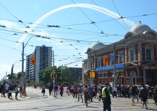 people walk down a street, no cars, police directing traffic, airplanes in formation and with white trails fly over the street part of the CNE air show flying over part of the Labour Day parade