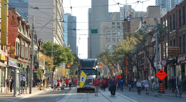looking east on Queen Street West towards the Labour Day parade. A large truck is in the middle of the road, and people waving flags are walking in front of it. Lots of people walking beside it and behind it. Stores on Queen Street to the sides, taller buildings in the background.