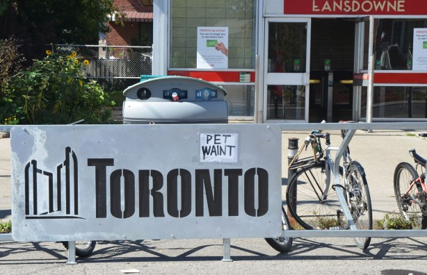 a sign that says pet waint on a sign that says Toronto in front of Lansdowne subway station entrance
