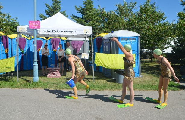 three women dressed in flippers, bathing suits and bathing caps pass by The Privy People, an act that is also very functional, porta potties decorated with artists work on the inside, personal service by people