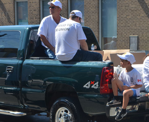 two men sitting in the back of a pick up truck as well as a boy sitting on the tailgate, in a parade, wearing white t-shirts that say Proud to be Union