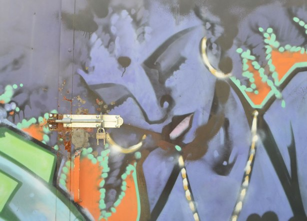 street art painting of part of a woman's face, in purple . eyes closed, looking down, with hew lock and key on the door that she's painted on, wearing a necklace